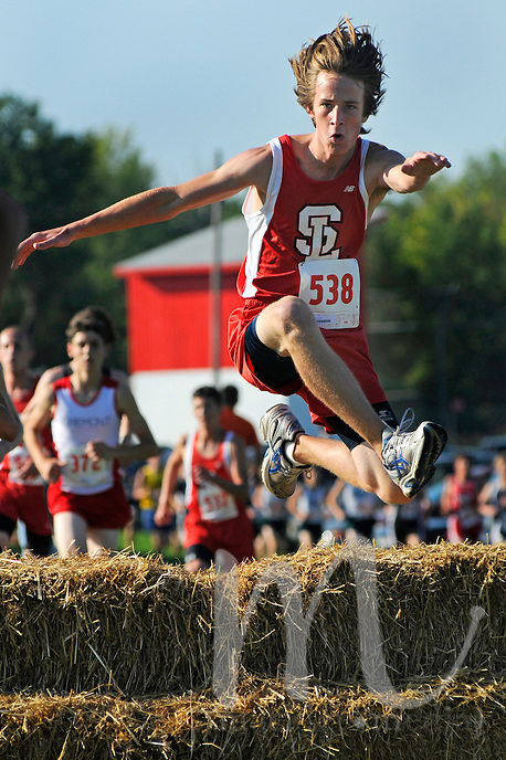 Spring Lake's Andrew Cole hurdles some hay bales during the Hill and Bale cross country invitational at Fremont Middle School on Saturday. ..Date Shot: 09/12/09