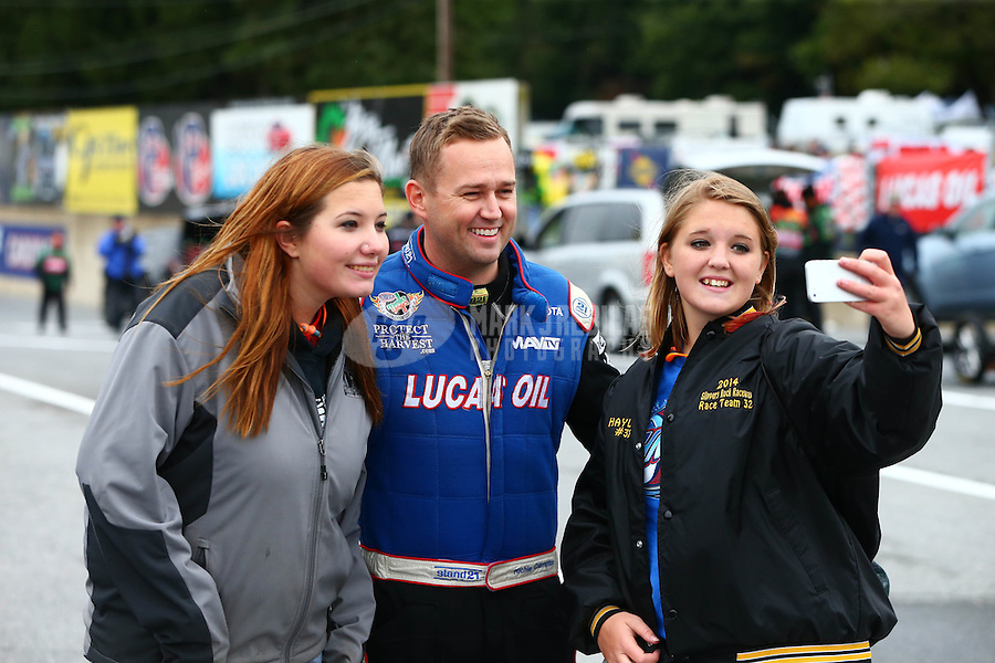 Oct 3, 2015; Mohnton, PA, USA; NHRA top fuel driver Richie Crampton (center) takes a selfie with fans during qualifying for the Keystone Nationals at Maple Grove Raceway. Mandatory Credit: Mark J. Rebilas-USA TODAY Sports