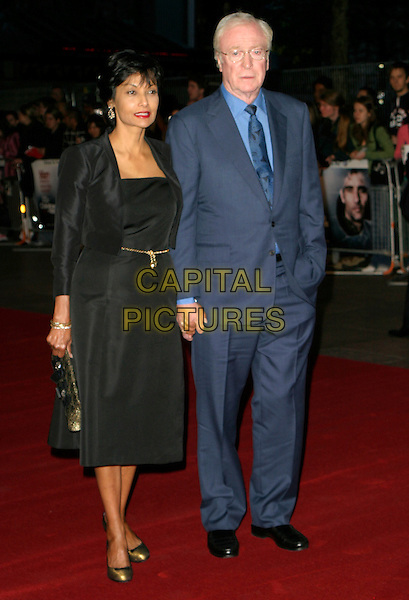 "SHAKIRA CAINE & SIR MICHAEL CAINE.Arrivals - ""Children Of Men"" Premiere,.Odeon Leicester Square Cinema, .London, England, September 19th 2006..full length married husband wife black dress blue suit tie.Ref: AH.www.capitalpictures.com.sales@capitalpictures.com.©Adam Houghton/Capital Pictures."