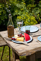 A selection of cheese is served with olive oil on a rustic wooden table in the garden