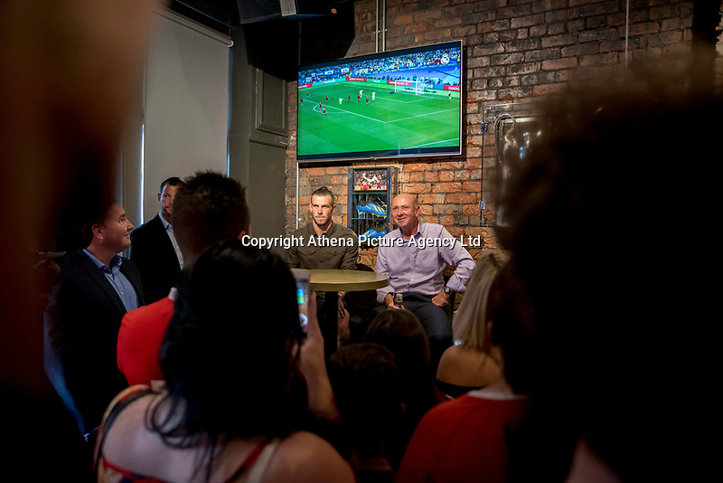 """Pictured: Gareth Bale speaks to Ian Gwyn Hughes from the FAW at his Elevens Bar in Cardiff, Wales, UK. Thursday 12 July 2018<br /> Re: Last night (Thurday 12 July) Elevens Bar & Grill and the Football Association of Wales jointly hosted a Q&A evening with Gareth Bale. At the event, Gareth unveiled a new piece of memorabilia for Elevens – his match worn boots from this year's Champions League Final with which he scored that incredible overhead kick.<br /> The event, hosted at Elevens Bar & Grill was open to members of the public with doors opening at 6pm on Thursday evening. People started queueing from 3pm, with a cross-section of fans of all ages in Wales shirts and bucket hats. <br /> The Q&A, conducted by Ian Gwyn Hughes from the FAW, discussed all aspects of his career so far, from growing up in Cardiff to winning 4 Champions League medals with Real Madrid. On growing up in Whitchurch, Gareth said: """"My family were a huge influence on me growing up. My parents were so supportive, taking me here there and everywhere so I could play football. Growing up I can hardly remember not being with a football – I even took one to bed!""""<br /> There were a lot of youngsters in the audience, eager to hear from their hero. Gareth's advice to them? """"Work hard for what you want and who knows where that could take you.""""<br /> As a left-footer, Ryan Giggs,  Wales' national team manager was someone he looked up to growing up. Gareth mentioned it was great to beat Ian Rush's goal scoring record for Wales with his childhood idol as manager. """"I knew I'd levelled his record at half time, I needed one more to break it. The manager wanted to take me off but I said give me another 15 minutes to see if I can do it. Luckily on 61 minutes our goalkeeping coach took too long to do the substitution on the paper, so it gave me an extra minute. It worked out perfectly."""""""