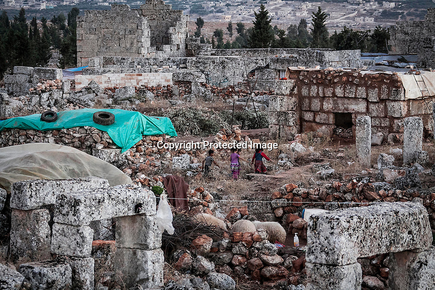 "In this Friday, Sep. 27, 2013 photo, Syrian displaced children walk at the sunset in the Kafr Ruma, an ancient roman ruins used as temporary shelter by those families who have fled from the heavy fighting and shelling in the Idlib province countryside of Syria. Dozens of families settled in the ancient ruins known as ""The Forgotten City"" and declared human heritage by UNESCO, when the clashes between opposition fighters and government forces broke out in the region since more than two years ago. (AP Photo)"
