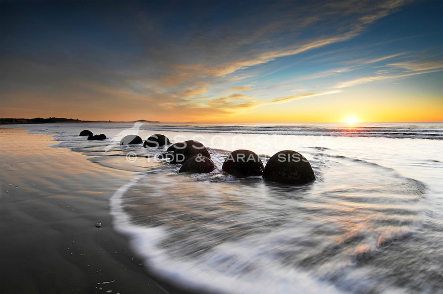 Group of round Moeraki Boulders at sunrise | sun star | waves & golden sky | South Island New Zealand