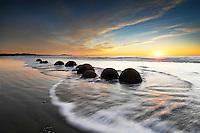 Group of round Moeraki Boulders at sunrise | sun star | waves & golden sky | South Island New Zealand