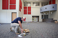 NWA Democrat-Gazette/DAVID GOTTSCHALK Cooper Bowerman, with Professional Cabling Solutions, puts in data drops Friday, July 14, 2017, inside the library of the new Farmington High School. Classes will be begin at the new school this August.