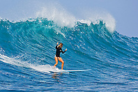Woman surfer, riding a rare big ocean wave in Kona Coast, Keauhou Bay, Big Island, Hawaii, Pacific Ocean.