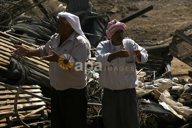 Palestinian men react on the remains of his tent destroyed by the Israeli army, in the West Bank village of Faresiya near Tubas, Monday, July 19, 2010. Israeli forces demolished a cluster of tents and shacks belonging to Palestinians in the northern West Bank . Photo by Wagdi Eshtayah