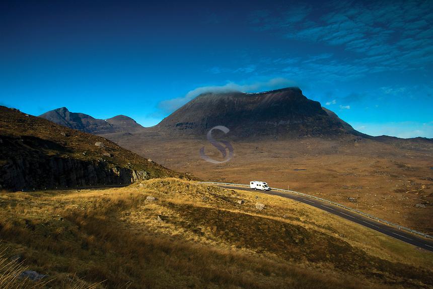A motorhome driving along the North Coast 500 beneath Quinag near Kylesku, Sutherland, Northwest Highlands