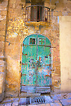 A green door and crumbling balcony of a building in Valetta, Malta.