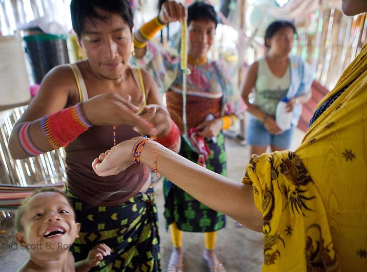 Woman tourist gets a traditional Kuna bracelet while visiting Rio Sidra, San Blas Islands, Kuna Yala, Panama