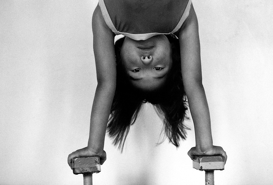 A young mongolian contortionist stands on her hands.