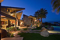 Night time view of luxury modern home and landscaping