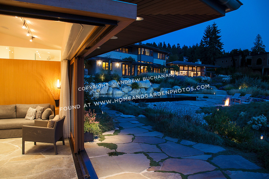 Sliding doors open a guest cottage to the pool and patio area of a waterfront home.