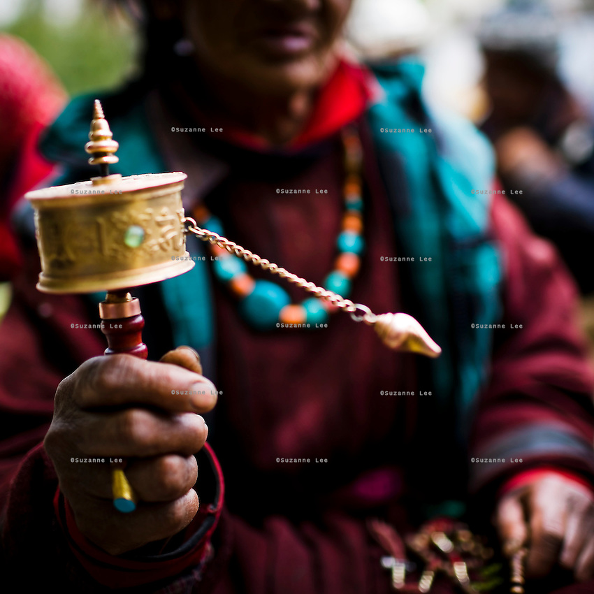 An elderly Ladakhi woman spins a handheld mani prayer wheel as she chants prayers in Chokhang Vihara, the central monastery in Leh town, Ladakh, Jammu & Kashmir, India, on 30th May 2009. Locals gather there to chant and pray together for the 6th Tara Ceremony 2009, which is presided over by a high lama, the venerable 9th Choegon Rinpoche.  Photo by Suzanne Lee
