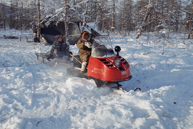 Even reindeer herders leave their winter camp on a snowmobile to check on their herd. N. Evensk, Magadan Region, E. Siberia, Russia