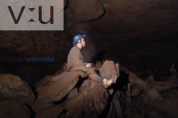 A spelunker takes a break on a rockpile at Sloans Valley Cave in Kentucky.