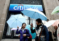 Pedestrians walk past a Citibank branch in Shanghai, China. Citigroup Inc. plans to increase its China headcount by one-third in 2007, as it opens new branches and boosts its small and medium-sized enterprise business. .