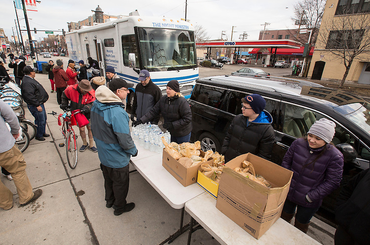 Members of the First Congregational Church of Western Springs hand our bag lunches as the Night Ministry's Health Outreach bus draws a crowd at Humboldt Park in Chicago during a Sunday afternoon stop March 29, 2015. (DePaul University/Jamie Moncrief)