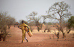 A woman walks to fetch water in Lugi, a village in the Nuba Mountains of Sudan. The area is controlled by the Sudan People's Liberation Movement-North, and frequently attacked by the military of Sudan.