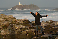A young woman enjoying the gale and storm force winds which create breakers, waves and rough seas off the north end of the island of Tresco, Isles of Scilly, Cornwall, UK.  The lighthouse on Round Island is in the distance.  03/12/06