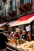 Women shopping at fresh fruit and vegetable stall at 'Il Capo' markets, in the historic quarter of Palermo, Sicily, Italy