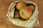 Brown paper bag overflowing with Russet apples with their pale brown and red and yellow skins sitting on chopping board