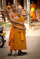 Young Buddhist monks in a friendly embrace. It is not uncommon to see this sort of affection amongst novice monks.  While they live a minimalist, sedentary life in the monastery, they welcome many of the 21st century conveniences like cell phones and internet...