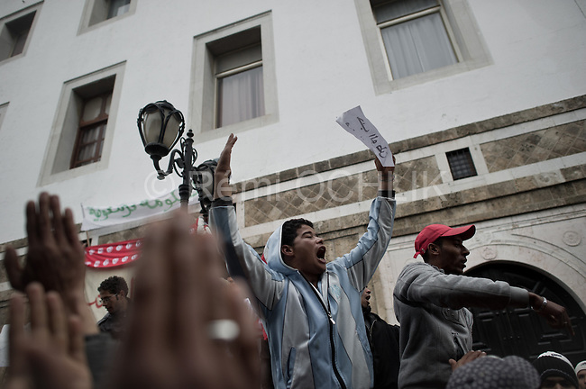 Remi OCHLIK/IP3 -  Protestors stand in front, to demand removal Protestors stand in front of the Prime Minister's office in Tunis, Tuesday, Jan. 25. 2011 to demand the removal of members of the ousted president's regime still in the government. Many people, bundled up in blankets, slept outside the prime minister's office overnight, in defiance of a curfew initiated in response to unrest that forced President Zine El Abidine Ben Ali to flee Tunisia on Jan. 14.