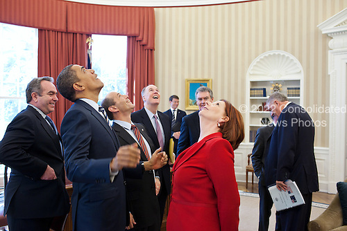 United States President Barack Obama, Prime Minister Julia Gillard of Australia, and members of the Australian and American delegations look up at the presidential seal in the Oval Office ceiling following their bilateral meeting, March 7, 2011..Mandatory Credit: Pete Souza - White House via CNP