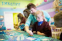 NWA Democrat-Gazette/CHARLIE KAIJO Melanie Hewins, owner and artist of Imagine Studios, (center) helps Katie Kelley, 8, (center right) create stencil art during a spring break art camp, Monday, March 19, 2018 at the Imagine Studios in Rogers. <br /><br />Melanie Hewing, owner and artist of Imagine Studios, worked as a literacy facilitator at Rogers High School for seven years and during that time discovered a talent and love for creating art through a side business painting murals in children's bedrooms. <br /><br />People began to ask if she would provide art classes for them as word spread. She has had her studio, Imagine Studios, now for seven years where she hosts classes and camps for both kids and adults.