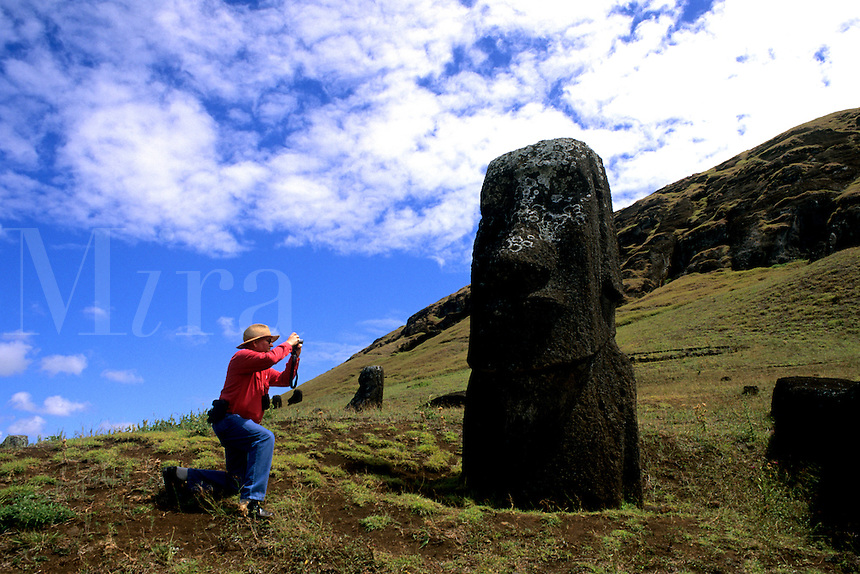 Retired tourist with camera at Rano Raraku Statues Easter Island during Tapati Festival Rapa Nui