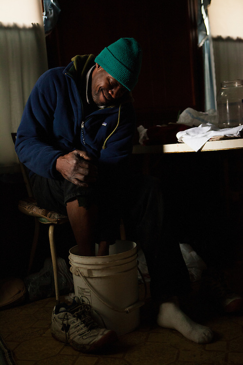 John Holt soaks his foot in a bucket of warm water he heated up over a fire. He lives in a house without electricity, heat, or running water. During the past winter his feet became frostbitten while he was collecting bottles to return for money. He now has to soak his right foot regularly to help it heal. If it doesn't heal, he'll need to have it amputated.