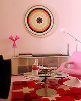 The living room is furnished with an eclectic mix of colourful pieces and 1960s style art