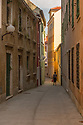 Zadar, Croatia. 14.10.2018. A woman walks down a narrow street in the Old Town, Zadar, Croatia. Photograph © Jane Hobson.