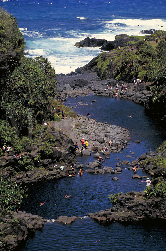 People swim or sun in Seven Pools of Kipahulu; surf beyond. Kipahulu Hawaii, Seven Pools of Kipahulu on Maui.