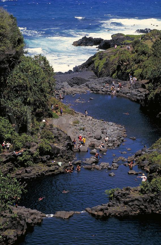 People swim or sun in Seven Pools of Kipahulu; surf beyond. Kipahulu Hawaii, Seven Pools of Kipahulu on Maui.