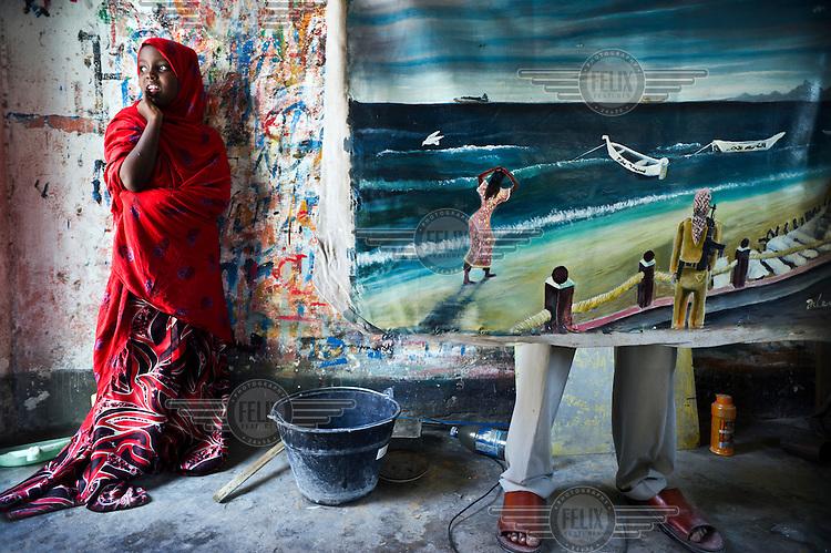 Artist Abdullah Abdirahman Abdullah Alif stands behind a painting at his friend's house in Mogadishu.