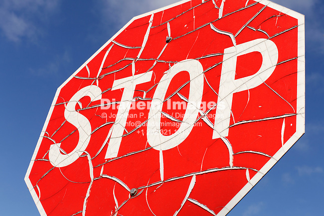 A cracked and worn stop sign against blue sky.