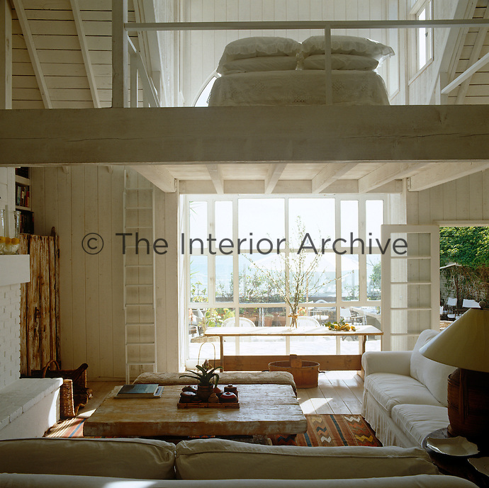 The bedroom of this open-plan beach house is situated on a wooden mezzanine and is accessed by a simple rustic ladder