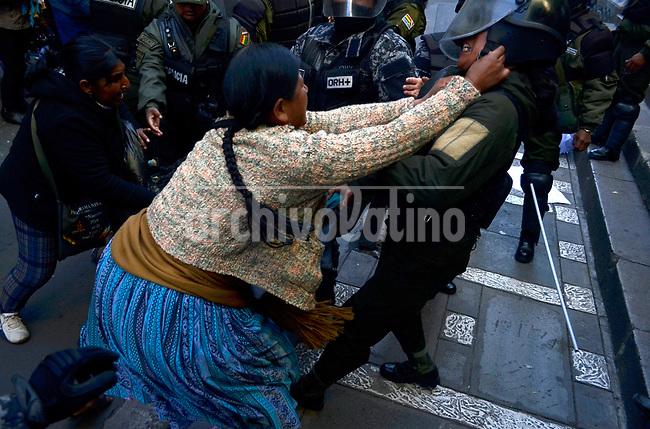 An aymara indian coca leaves grower flights with police during a protest in La Paz