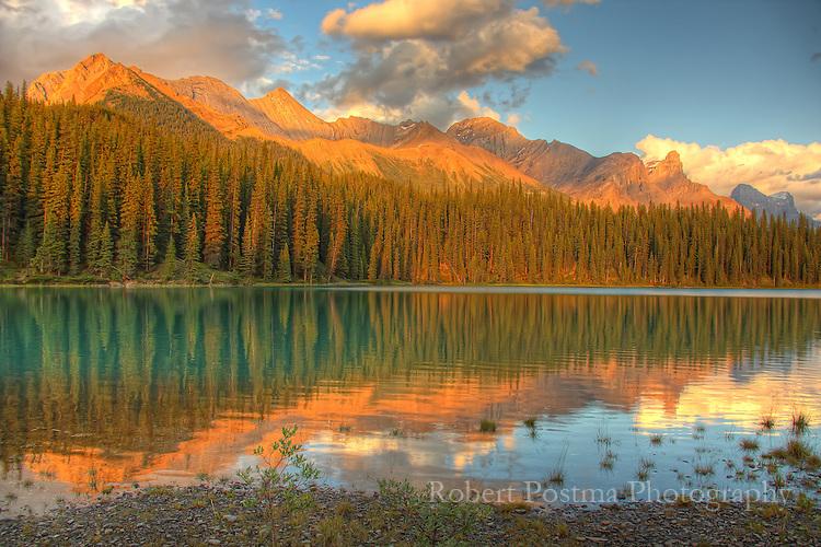The mountains surrounding Maligne Lake are lit but the setting sun, Jasper National Park.
