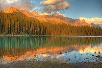 The mountains surrounding Maligne Lake are lit but the setting sun, Jasper National Park.