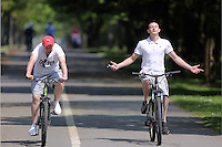 Two young men cycle by the coastal path enjoying the sunshine in Swansea, Wales, UK Friday 13 May 2016
