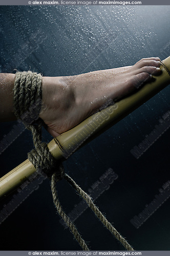 Closeup of wet woman feet tied with bondage rope to bamboo