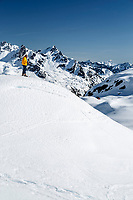 Spring landscape of man snow shoeing in the snow-covered Talkeetna Mountains in the Mint Glacier Area of the Hatcher Pass Managmement Area of the Matanuska Valley with the Mint Hut in background  Spring Southcentral, Alaska  Model Released<br /> <br /> Photo by Jeff Schultz (C) 2016  ALL RIGHTS RESERVED