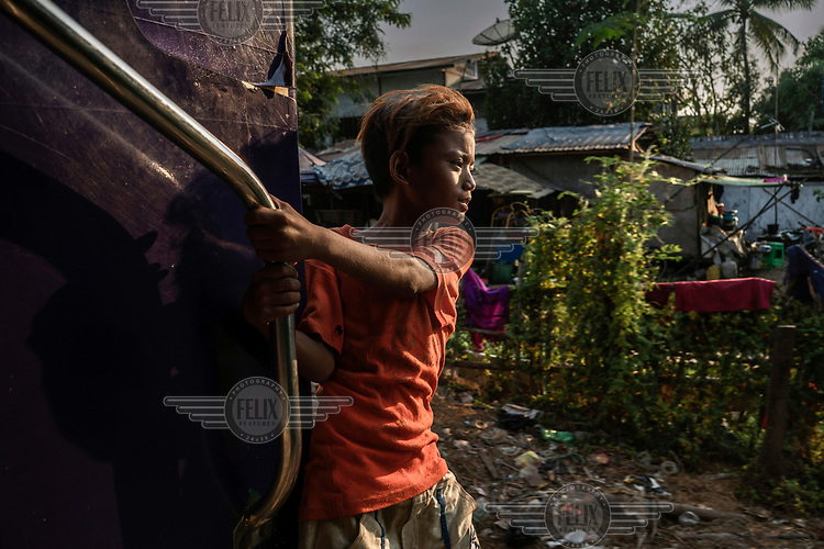 A boy hangs out of the door of a moving Yangon Circle Line train. Each day, around 100,000 people use the route despite its antiquated rolling stock and infrastructure. The commuter line loops around the city stopping at 38 stations and taking just under three hours to complete the 45 km (28 miles) circle.