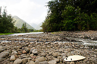 A person stands along the rocky stream at the mouth of Waipi'o River, Waipi'o valley, Hamakua District, Big Island.