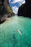 PHILIPPINES, Palawan, El Nido, Miniloc Island, a woman floats on her back in Big Lagoon on Miniloc Island located in Bacuit Bay in the South China Sea