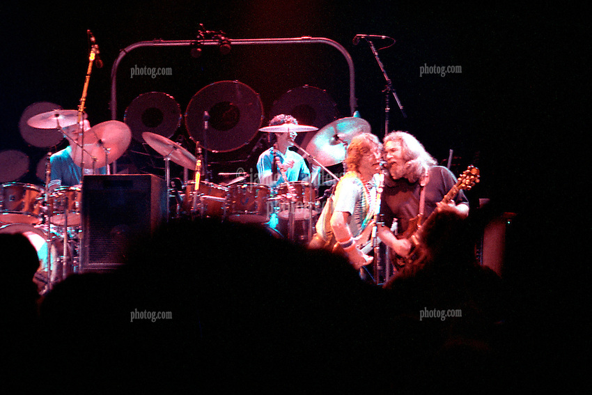Phil Lesh and Jerry Garcia, both singing into a single microphone. The Grateful Dead in Concert at the Saratoga Performing Arts Center, 24 June 1984
