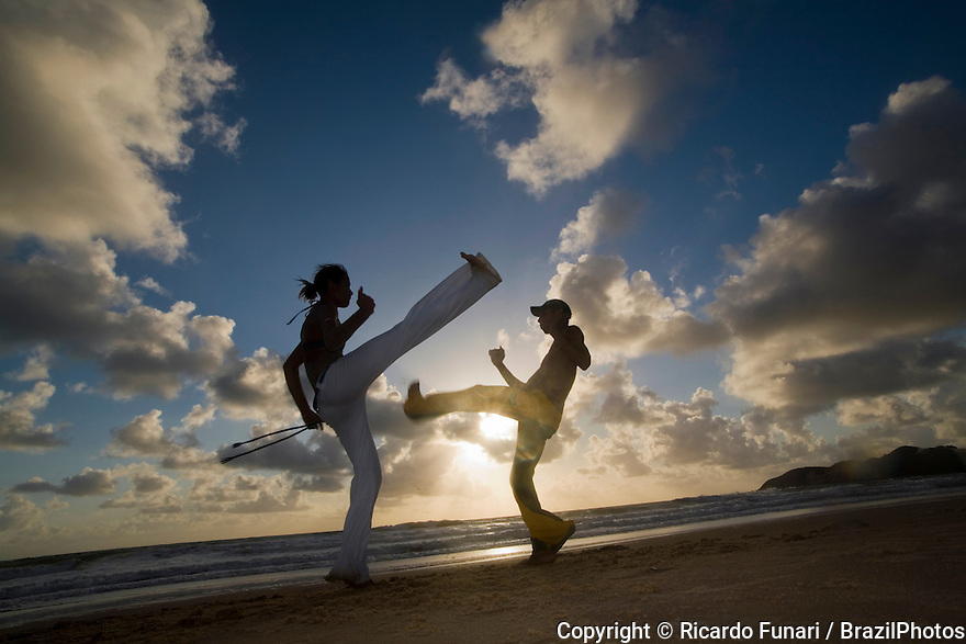 Capoeira is a Brazilian art form that combines elements of martial arts, sports, and music. It was created in Brazil mainly by descendants of African slaves with some very limited Brazilian native influences, probably beginning in the 16th century. It is known by quick and complex moves, using mainly kicks and quick leg sweeps, with some ground and aerial acrobatics, knee, take-downs, elbows, punches and headbutts. In the 16th century Portugal had one of the biggest colonial empires of the world, but it lacked people to actually colonize it. In Brazil the Portuguese colonists, like many European colonists, opted to use slavery to supply this shortage of workers. Colonists tried to enslave Brazilian natives in the beginning, but this quickly proved too difficult for many reasons, including the familiarity natives had with the land. The solution was importing slaves from Africa. In its first century the main economic activity in the colony was the production and processing of sugarcane. Portuguese colonists used to create large sugarcane farms called engenhos, farms which extensively used enslaved workers. Slaves, living in inhuman and humiliating conditions, were forced to work hard and often suffered physical punishment for any small misbehaviour. Even though slaves outnumbered the Portuguese colonists, the lack of weapons, the colonial law, the disagreement between slaves coming from different African cultures and their complete lack of knowledge about the land and its surroundings would usually discourage the idea of a rebellion. In this environment Capoeira began to develop. More than a fighting style, it was created as a hope of survival, a tool with which an escaped slave, completely unequipped, could survive in the hostile, unknown land and face the hunt of the capitaes-do-mato, colonial agents in charge of finding escapees, always armed and mounted.